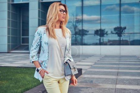 Photo pour Souriant belle femme à la mode dans des vêtements et des lunettes élégantes, debout contre un gratte-ciel . - image libre de droit
