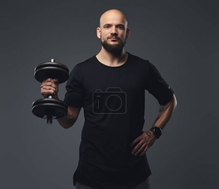 Photo for Close-up portrait of a handsome bearded athlete in a black t-shirt, posing dumbbell in a studio. Isolated on a gray background. - Royalty Free Image