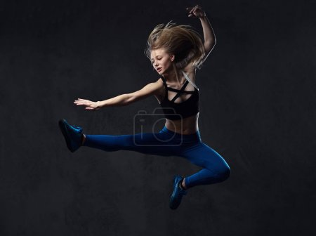 Young blonde ballerina in sportswear dances and jumps in a studio. Isolated on a dark background.