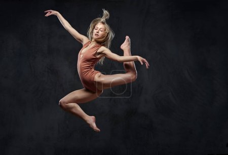 Young graceful ballerina dances and jumps in a studio. Isolated on a dark background.