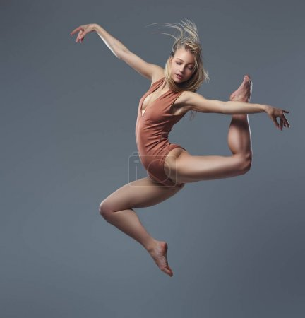 Young graceful ballerina dances and jumps in a studio. Isolated on a gray background.