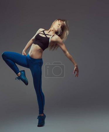 Young blonde ballerina in sportswear dances in a studio.