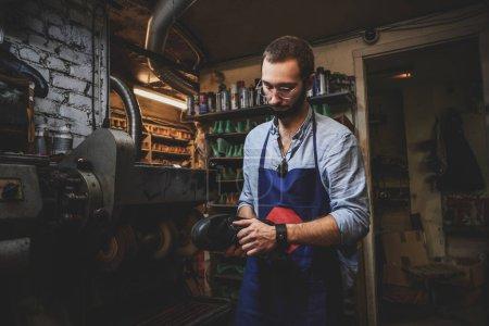 Photo pour Le cordonnier porté en lunettes crée de nouvelles paires de chaussures à l'aide d'une machine spéciale. - image libre de droit