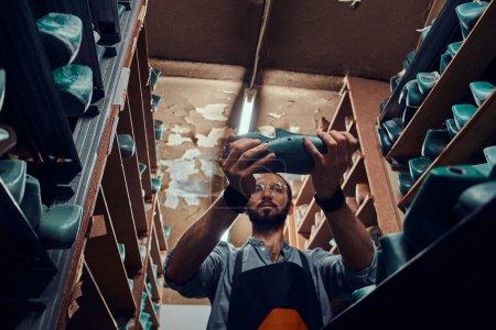 Photo pour Le cordonnier diligent trouve une forme de chaussure adaptée à son nouveau projet à l'entrepôt. - image libre de droit