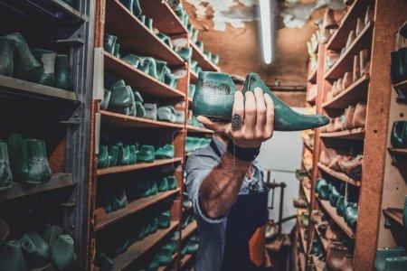 Photo pour Le cordonnier talentueux a finalement trouvé la forme de chaussure qui convenait à son nouveau projet d'entreposage. - image libre de droit