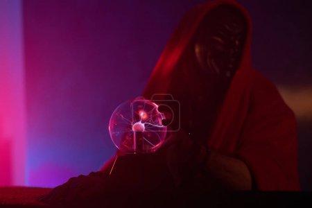 Photo pour Magicien en masque effrayant tient globe magique, entouré de lumière rose brumeuse . - image libre de droit