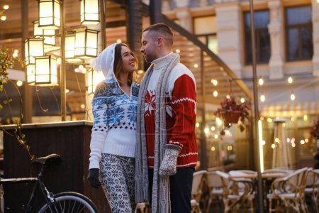 Photo for Lovely couple feels happy on the Christmas market, surrounded with warm lights. - Royalty Free Image