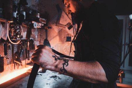 Photo pour Dans l'atelier occupé maître talentueux fait son maître paix à partir de cuir . - image libre de droit