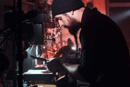 Photo pour Maître de cuir expérimenté travaille sur son nouveau projet à l'atelier sombre . - image libre de droit