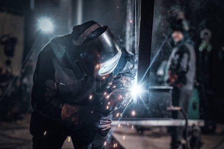 Photo pour L'homme travaille à l'usine de métal, il soude un morceau de rail à l'aide d'outils spéciaux . - image libre de droit