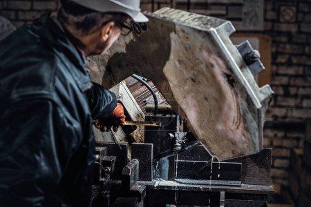 Photo pour Un travailleur expérimenté travaille dans une usine métallurgique à l'aide d'une machine-outil spéciale. - image libre de droit