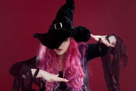 Attractive woman in witches hat and costume with red hair performs magic above the surface of the mirror, place for your text or photo manipulation