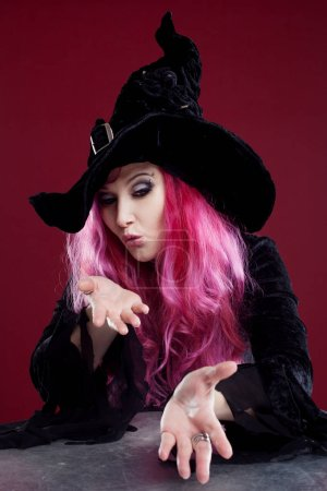 Attractive woman in witches hat and costume with red hair blows away something with hands, place for your text or photo manipulation