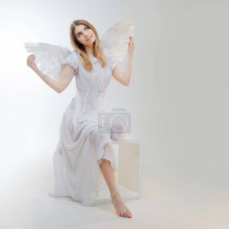 Young, wonderful blonde girl in the image of an angel with white wings.