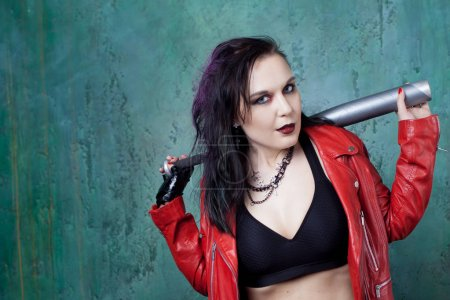 Punk woman with a bat in red leather jacket, standing against the wall