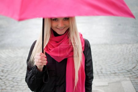 Sad pensive girl standing under a bright umbrella on the street. The concept of positivity and optimism. Girl in a bright pink scarf and umbrella walking in a rainy city.