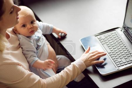 Young beautiful blonde woman, mother in home office with computer and her baby. Work and child care.