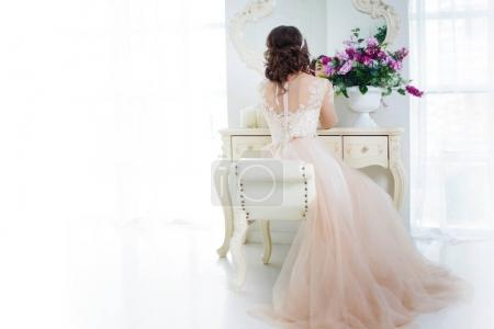 Beautiful girl bride in wedding gown sits at dressing table. Back view. Free space left