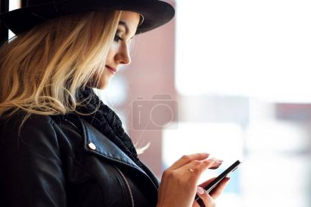 Trendy girl in the hat, outdoor. Young woman uses phone. Portrait in profile