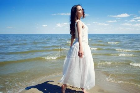 Young beautiful brunette woman in white dress on the seashore