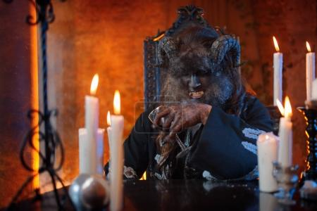 man in image of monster with horns sitting at table with a glass in hand, alcohol