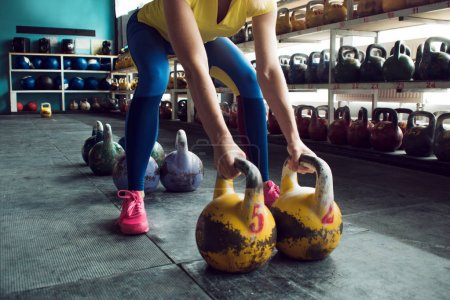 Kettlebell club. Girl is getting ready to do a workout with weights, push long cycle