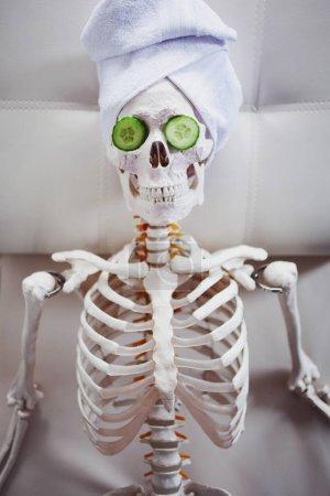 Photo pour Squelette dans le salon Spa avec serviette sur la tête et masque sur le visage, se détend. Un concept absurde, une parodie sociale. Prenez soin de la beauté et oubliez la paix intérieure - image libre de droit