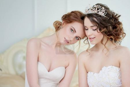 Two girls in wedding dresses. Beautiful delicate girls in the Bridal salon