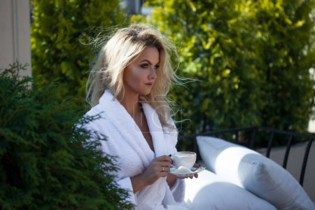Beautiful young woman in Bathrobe sitting on terrace and drink coffee