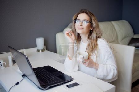 Photo pour Étudiant ou pigiste, travaillant à la maison avec un ordinateur portable. Charmante jeune femme assise avec une tasse de café . - image libre de droit
