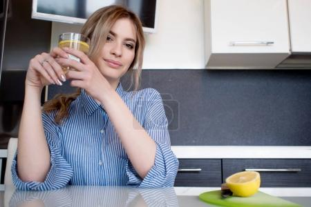 Beautiful girl starts her morning with a glass of water with lemon