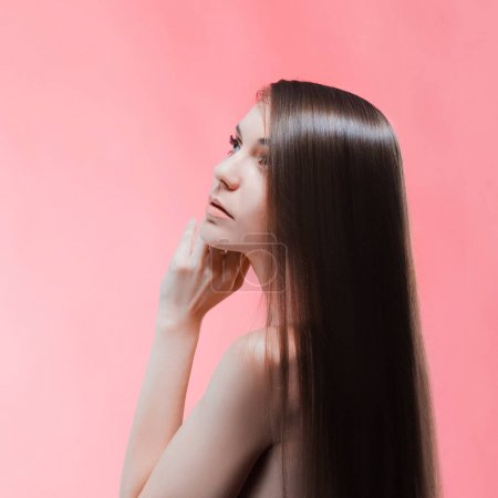 Beauty portrait of brunette with perfect hair, on a pink background. Hair care