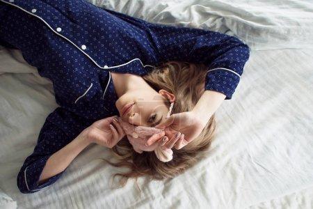 Photo pour Cute blonde dans son lit en pyjama bleu et masque de sommeil - image libre de droit