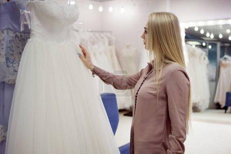 Beautiful girl chooses her wedding dress. Young woman entrepreneur. Portrait in Bridal salon