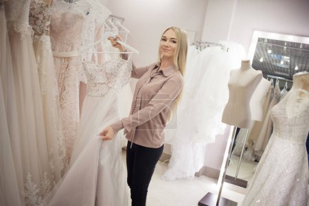 Successful young business woman in her Bridal salon. Beautiful girl entrepreneur. Choose an outfit for wedding