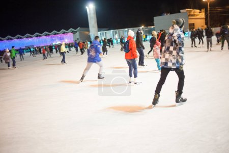 MOSCOW, RUSSIA - NOVEMBER 20, 2016: A lot of people riding on public ice rink in Sokolniki Park in Moscow