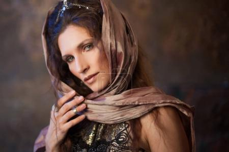 Portrait in the shawl. Tribal dancer, beautiful woman in the ethnic style on a textured background