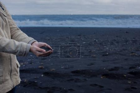 Black volcanic sand in the hands of the traveler. Iceland, beach of Vik