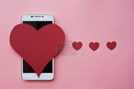 Photo pour Beaucoup de cœurs et smartphone. Le concept à aimer dans les réseaux sociaux ou l'application Sortir ensemble - image libre de droit