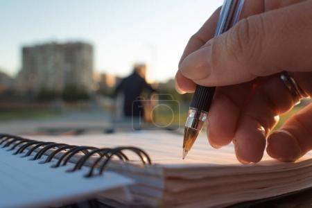 Close-up, writing in a notebook, develop plan of action