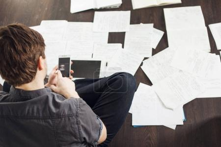 Young male entrepreneur makes brainstorming sitting on the floor in the apartment. Creative approach to business
