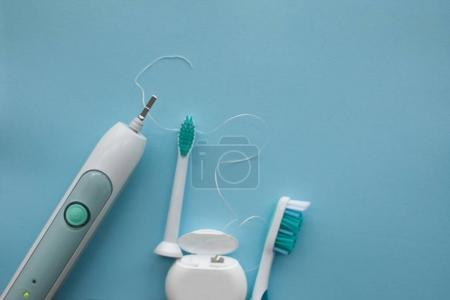 A set of sonic toothbrush, dental floss and classic toothbrush