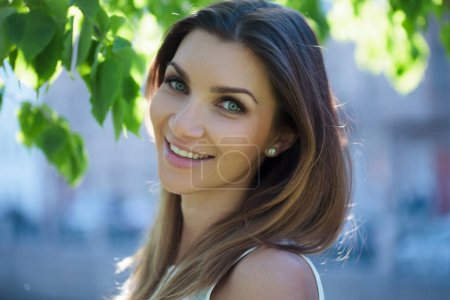 Close-up portrait of a beautiful woman, brunette. On a background summer nature