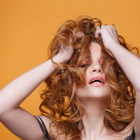 Photo for Happy redheaded young woman with luxurious curly hair. Studio portrait on yellow background. - Royalty Free Image