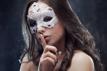 Mysterious and beautiful brunette with Venetian mask.