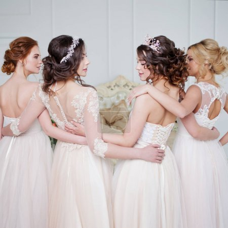 Bride in wedding salon. Four beautiful girl are in each other's arms. Back, close-up lace skirts