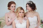 Three girls in wedding dresses. Beautiful delicate girls in the Bridal salon