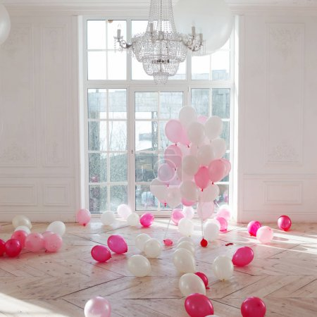Luxurious living room with large window to the floor. Palace is filled with pink balloons