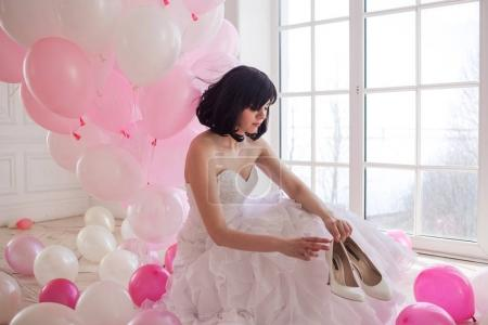 Young woman in wedding dress in luxury interior with a mass of pink and white balloons. Hold in hands her white shoes