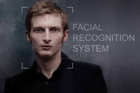 Facial recognition system, concept. Young man on grey background, face recognition